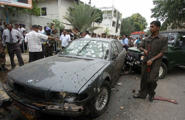 A Sri Lankan soldier stands alert beside the bomb damaged vehicle of Sri Lankan Defence Ministry Secretary Gotabaya Rajapakse after a suicide bomb attack in Colombo, 01 December 2006. A suspected Tamil suicide bomber attacked a defence ministry convoy carrying the president's brother, killing at least one soldier, police said. Gotabaye Rajapakse, secretary to the defence ministry and brother of President Mahinda Rajapakse, was unhurt after the blast in the heart of the Sri Lankan capital. AFP PHOTO/Lakruwan WANNIARACHCHI. (Photo credit should read LAKRUWAN WANNIARACHCHI/AFP/Getty Images)